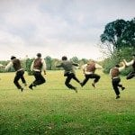 Groom and groomsmen jump high in green grass during wedding ceremony in Nashville Tennessee