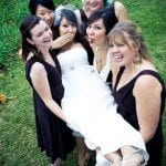 Bridesmaids hold bride up in green field at wedding ceremony in Nashville Tennessee