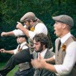 Groom and groomsmen jump in green field at wedding ceremony in Nashville Tennessee