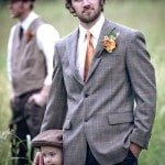 Groom stands with child in grassy field at wedding ceremony in Nashville Tennessee