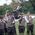 Groomsmen hoist groom up in grassy field at wedding ceremony in Nashville Tennessee