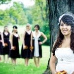 Bride stands in front of tree with bridesmaids in back ground at wedding in Nashville Tennessee
