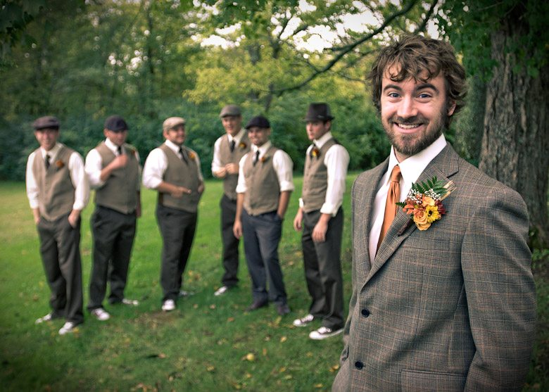 Groom smiles with groomsmen in green grass during wedding ceremony in Nashville Tennessee