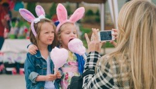 Blonde mother takes picture on smart phone of two young children in bunny ears eating cotton candy at holiday event in Nashville Tennessee